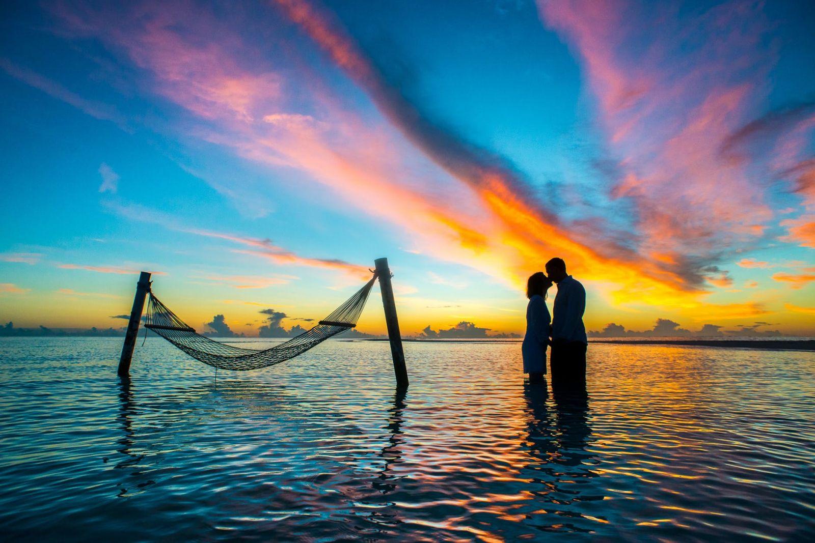 Zaljubljeni par uživa u vodi uz romantičan zalazak sunca