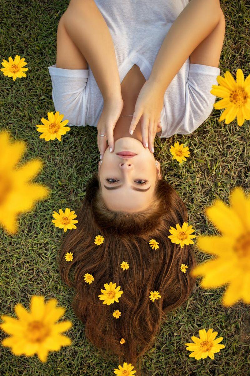 Devojka sa cvećem u kosi leži na travi